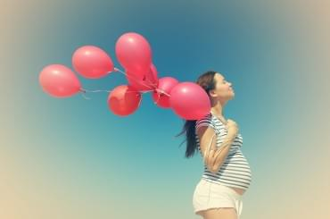 Pregnant woman holding red balloons